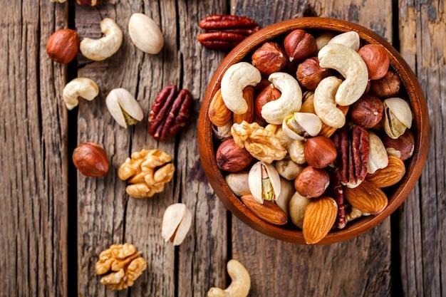 Орехи, смешанные в деревянной тарелке. ассортимент Premium Фотографии
