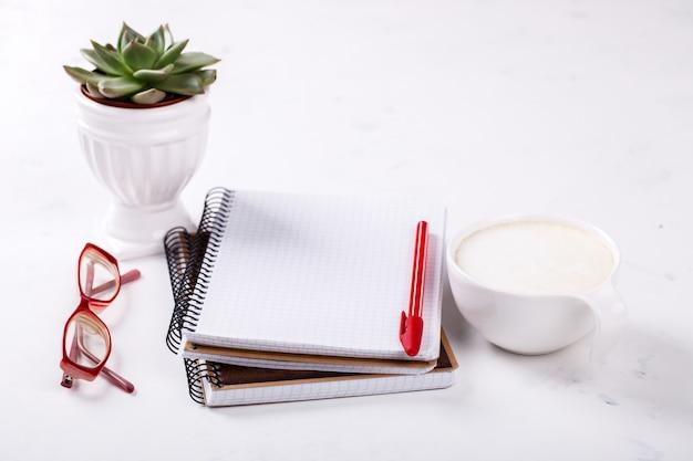 ペン、メガネ、コーヒー、花とメモ帳ビジネスコンセプト Premium写真
