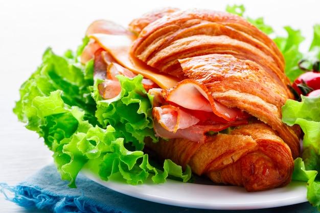Свежий круассан сэндвич с ветчиной, сыром Premium Фотографии