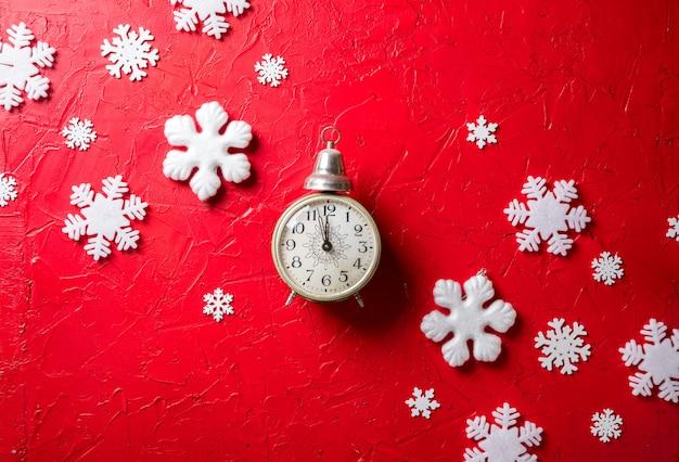 紙の雪と赤い背景の時計 Premium写真
