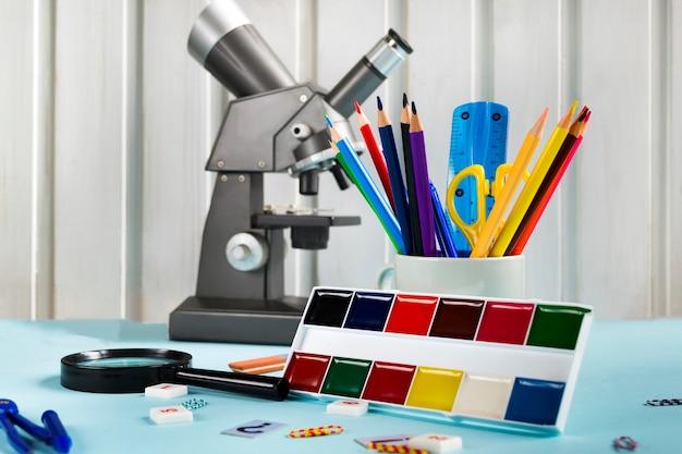 色鉛筆、はさみ、定規、顕微鏡、青色の背景にペイントします。学校付属品、学用品のセット Premium写真