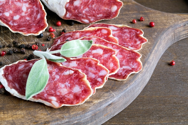 木製の背景にスパイスとフレンチチーズ乾燥サラミのスライス Premium写真