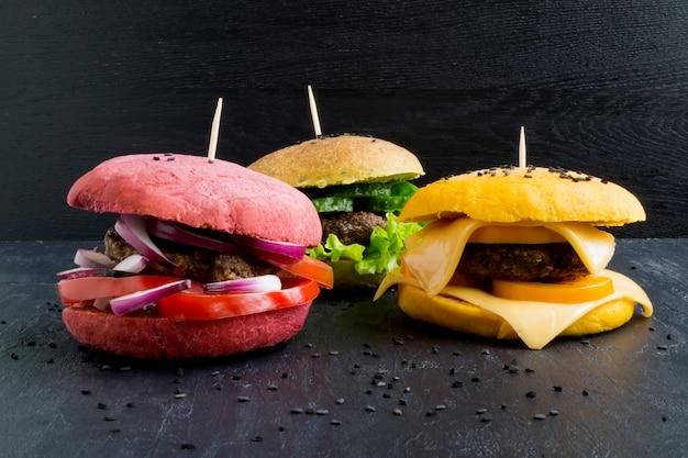 Гамбургеры с цветными булочками. Premium Фотографии