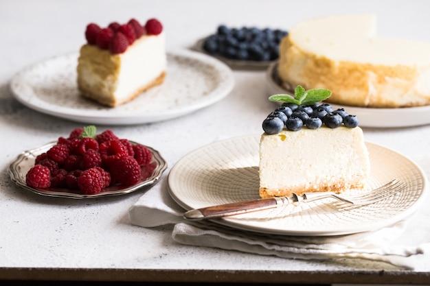 ブルーベリーとラズベリーホワイトプレート上の古典的なニューヨークチーズケーキのスライス。クローズアップビュー。ホームベーカリー Premium写真