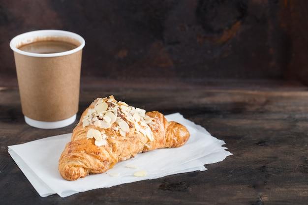 焼きたてのクロワッサンと暗闇の中で紙コップのコーヒー Premium写真