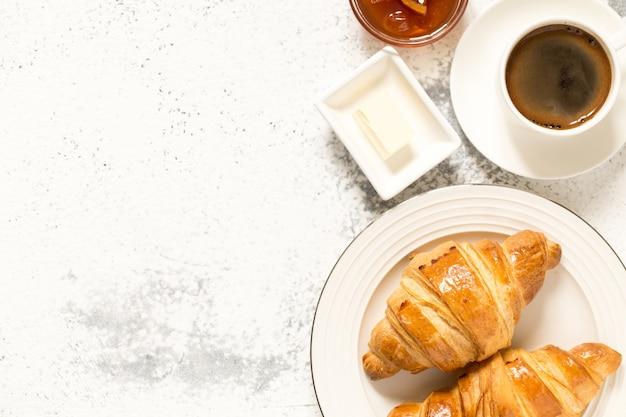 クロワッサンと朝食。焼きたてのクロワッサンとコーヒー、上面図。 Premium写真