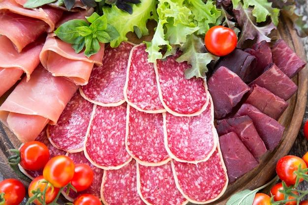 ハム、サラミ、ブレサオラの前菜。トマトとバジル。セレクティブフォーカス Premium写真