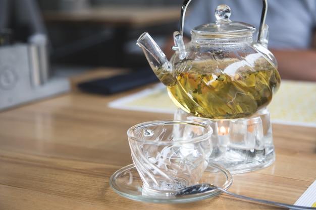 ガラスのティーポットとガラスのカップとハーブティー Premium写真