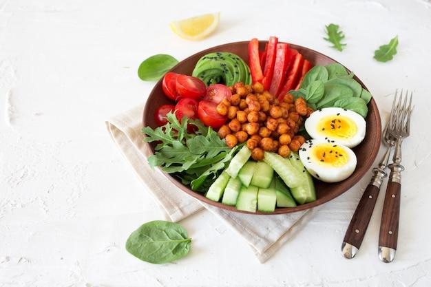 Чаша будды, здоровая и сбалансированная еда. жареный нут, помидоры черри, огурцы, паприка, яйца, шпинат, руккола Premium Фотографии