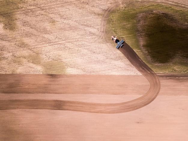 畑、農業分野でのトラクターの空撮。トラクター育成フィールド、空撮 Premium写真