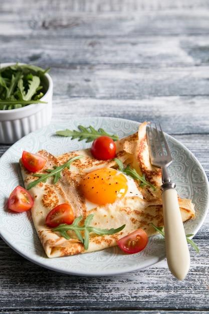 卵、チーズ、ルッコラの葉とトマトのクレープ。ガレットが完成しました。 Premium写真