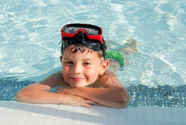 カメラを見ながらスイミングプールに男の子のビューの上 Premium写真