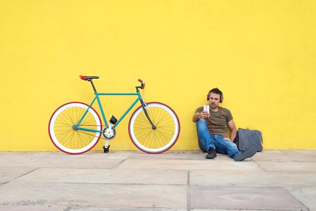 トレンディな表情で床に座って魅力的な男の正面図 Premium写真