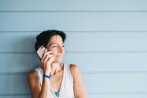 木製パネルの壁にもたれながら携帯電話で話している夏のドレスの若い成人女性 Premium写真