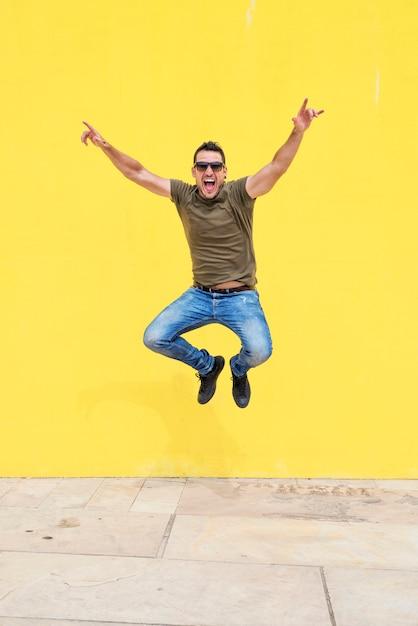 晴れた日に黄色の明るい壁に対してジャンプサングラスをかけている若い男の正面図 Premium写真