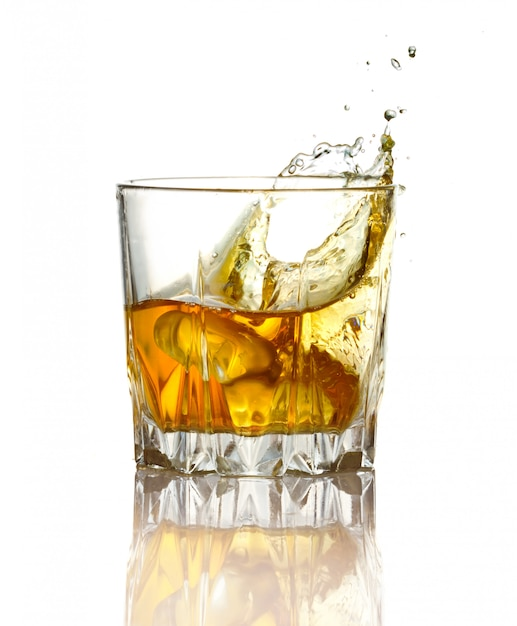 ガラスのウイスキーと分離された氷のしぶき Premium写真