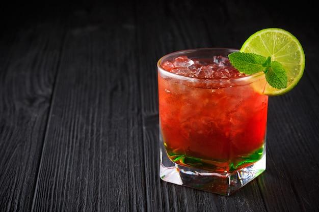 Красный алкогольный коктейль с мятой и лаймом на черном фоне Premium Фотографии