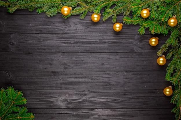 黒の木製の背景にクリスマスのモミの木 Premium写真