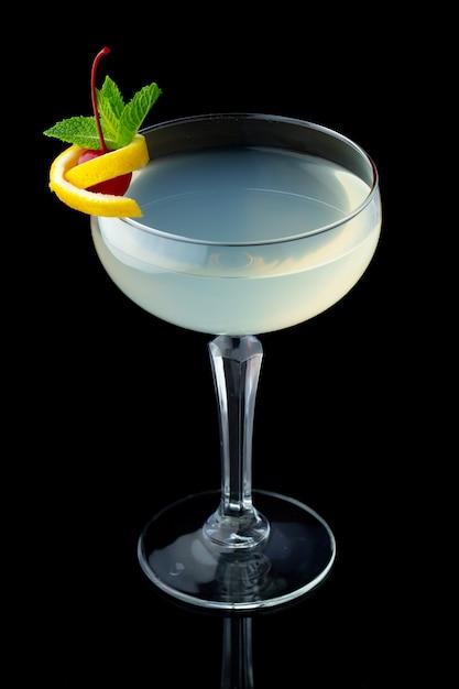 Прозрачный алкогольный коктейль с мятой и вишней на черном фоне Premium Фотографии