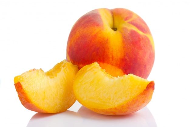 白で隔離されるスライスと熟した桃の果実 Premium写真