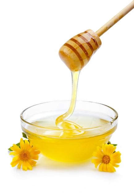 分離されたガラスのボウルに木製のひしゃくから注ぐ甘い蜂蜜 Premium写真