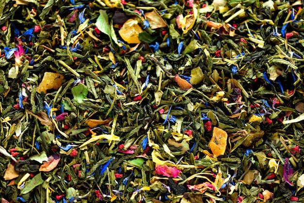 青い花、カレンデュラ、コーンフラワーの乾燥花びらと緑茶のテクスチャ。フード。有機性健康的なハーブの葉、デトックスティー。 Premium写真
