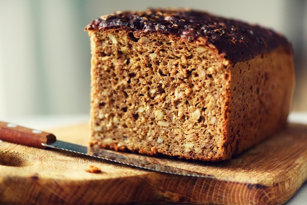 女性の手が焼きたてのパンをスライスします。手作りの茶色のパン、ベーカリーのコンセプト、自家製食品、健康的な食事コピースペース Premium写真