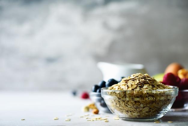 オートミール、灰色のコンクリート背景にオート麦フレーク。健康的な朝食のコンセプトです。 Premium写真