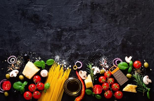 イタリアのパスタ、黒の背景にスパゲッティの食材。 Premium写真