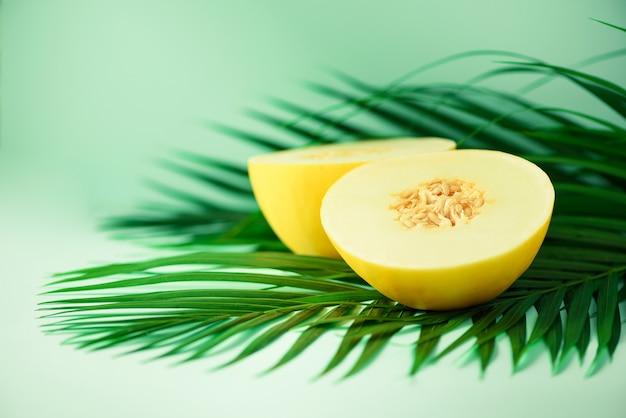 熱帯の緑のヤシの葉の上の甘いメロン。ポップアートデザイン、創造的な夏のコンセプト。生ビーガンフード Premium写真
