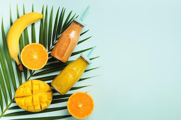 Свежий апельсин, банан, ананас, манго пюре и сочные фрукты на пальмовых листьях на синем фоне. детокс летний напиток. Premium Фотографии