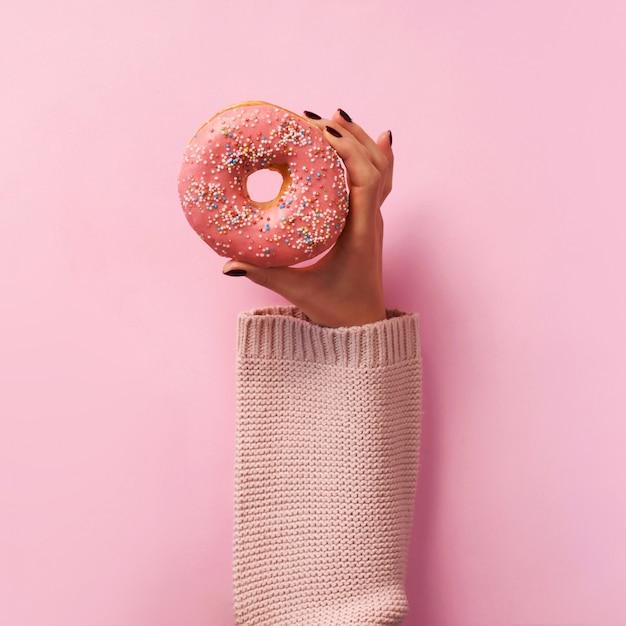女性の手はピンクの背景の上にドーナツをかざす。 Premium写真