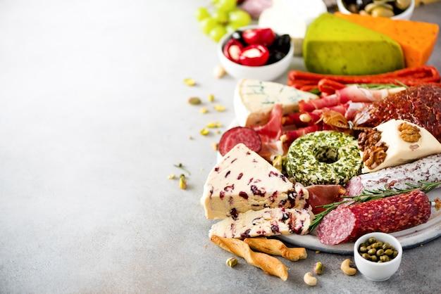 伝統的なイタリアの前菜、サラミ、まな板、生ハム、ハム、チーズ、オリーブ、ケッパー付きまな板 Premium写真