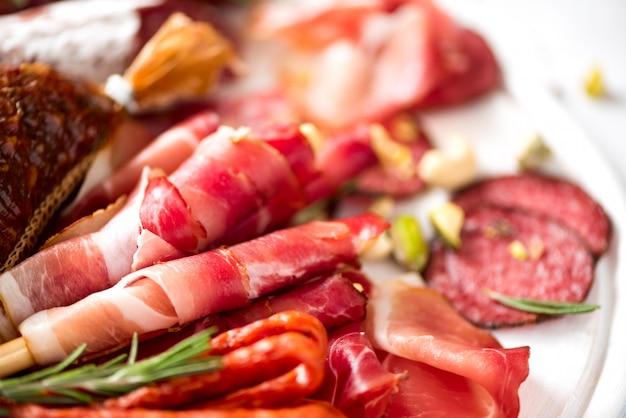 冷製スモークミートプレート。伝統的なイタリアの前菜、サラミ、生ハム、ハム、ポークチョップ、灰色の背景にオリーブのまな板。平面図、コピースペース、平干し Premium写真