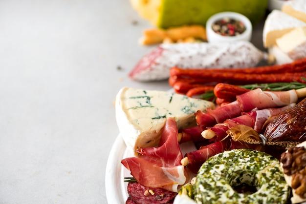 伝統的なイタリアの前菜、サラミ、生ハム、ハム、ポークチョップ、オリーブとまな板 Premium写真