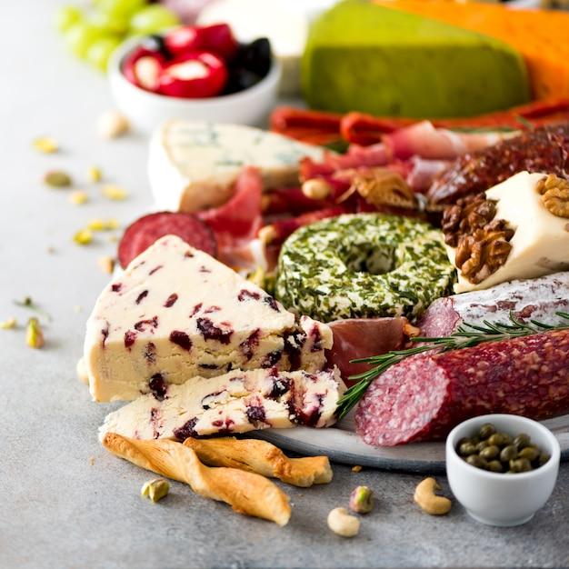 伝統的なイタリアの前菜、サラミとまな板、冷たい燻製肉、生ハム、ハム、チーズ、オリーブ、灰色の背景にケッパー。チーズと肉の前菜スクエアクロップ Premium写真