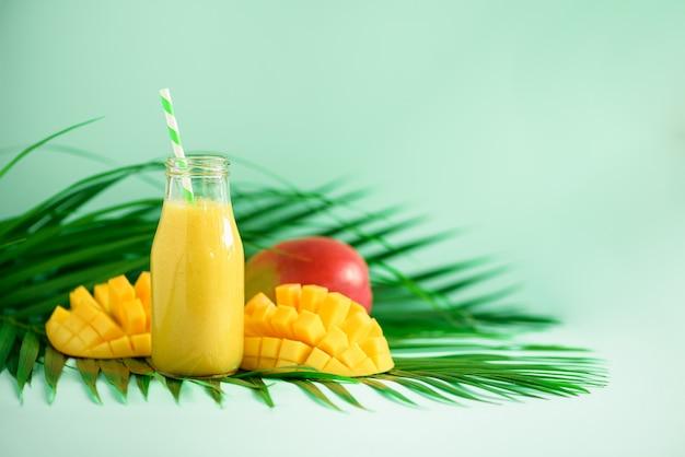 オレンジ色の果物とマンゴーのおいしいジューシースムージー。ポップアートデザイン、創造的な夏のコンセプト。緑のヤシの葉の上のガラス瓶の中のフレッシュジュース。 Premium写真