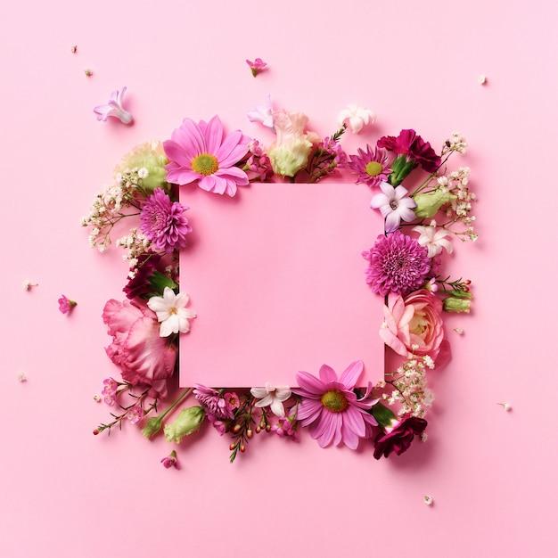 パンチの効いたパステル調の背景にピンクの花のフレーム。バレンタインデー、女性の日のコンセプト Premium写真
