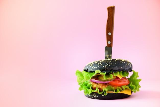 Концепция быстрого питания. сочный черный бургер с ножом на розовом фоне. забери еду. нездоровая диета кадр с копией пространства Premium Фотографии