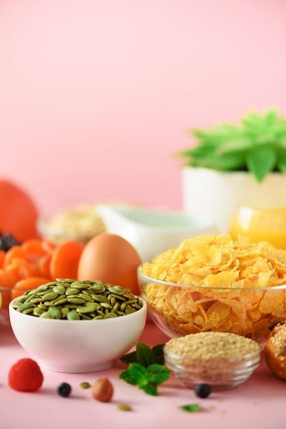 コーンフレークミルク、新鮮な果実、ヨーグルト、ゆで卵、ナッツ、フルーツ、オレンジ、バナナ、黄色の背景に朝食用ピーチ。スペースをコピーします。健康食品のコンセプトです。 Premium写真