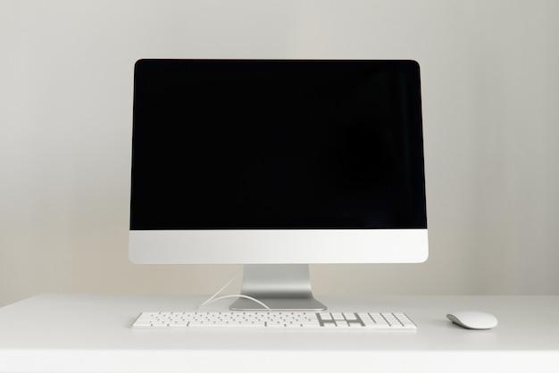 Клавиатура, мышь, дисплей компьютера с черным пустым экраном. передний план. дизайнерское рабочее пространство на сером фоне. минималистичный домашний офис. Premium Фотографии
