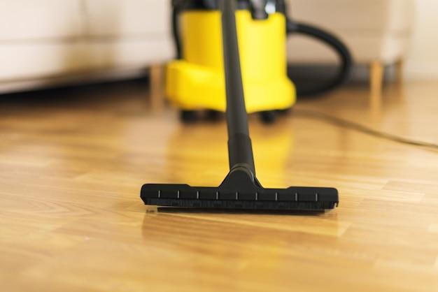 黄色い掃除機でリビングルームを掃除する保護手袋の女。 Premium写真