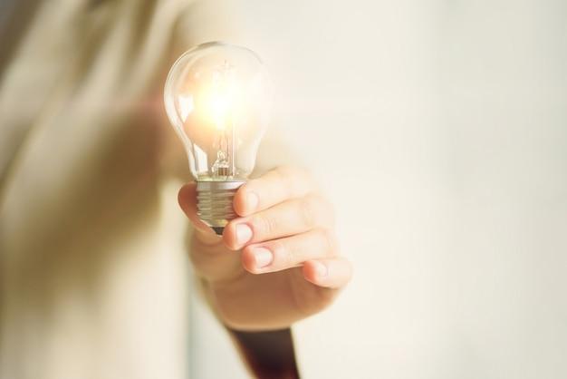 Женщина рука лампочку на кремовом фоне. креативная идея, новый бизнес-план, мотивация, инновации, концепция вдохновения. Premium Фотографии