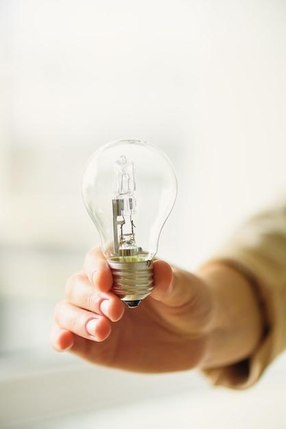 Женщина рука лампочку на крем фон с копией пространства. креативная идея, новый бизнес-план, мотивация, инновации, концепция вдохновения. Premium Фотографии