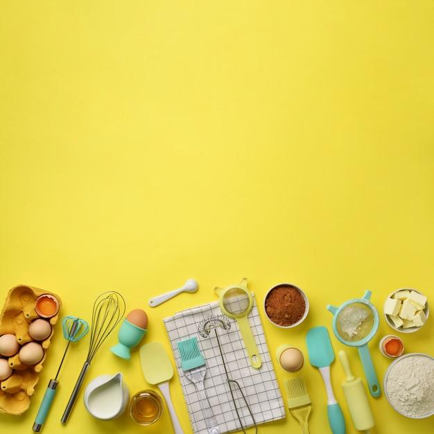 スクエアクロップベーキング成分 - バター、砂糖、小麦粉、卵、油、スプーン、麺棒、ブラシ、泡立て器、黄色の背景上のタオル。 Premium写真