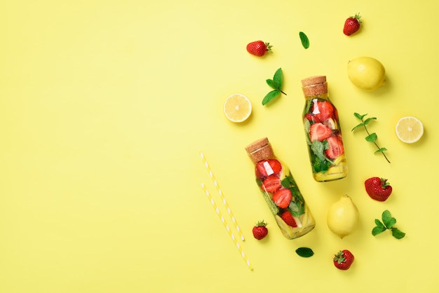 ミント、レモン、イチゴのデトックスウォーターのボトル。柑橘類のレモネード。夏の果物は水を注入しました。 Premium写真