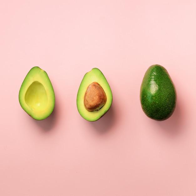 Органический авокадо с семенами, половинки авокадо и целые фрукты на розовом фоне. зеленый авокадо шаблон в стиле минимальной плоской планировки. Premium Фотографии