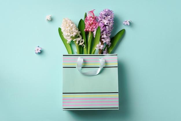 青いパンチの効いたパステル調の背景に買い物袋に新鮮なヒヤシンスの花。クリエイティブなレイアウト Premium写真