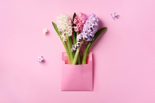 パンチの効いたパステル調の背景にピンクの郵便封筒の春のヒヤシンスの花。 Premium写真