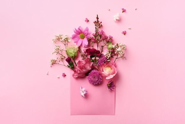 Розовый конверт с весенними цветами. Premium Фотографии